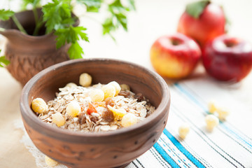 Corn flakes in ceramic bowl and apples