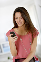 Beautiful young woman sending message with smartphone