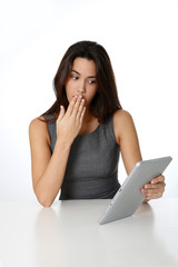 Brunette girl with shocked expression at looking at tablet