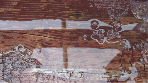 Water Dripping in Puddle on Rustic Deck