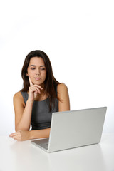 Young woman with thoughtful look in front of laptop