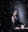 A sexy redhead woman in erotic fur on a snowy background