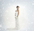 A young bride in a white dress on a snowy background