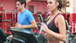 Woman and man running on a treadmill