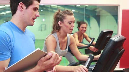 Trainer teaching two women on exercise bikes