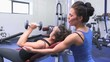 Trainer helping woman lifting weights