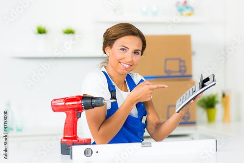 heimwerkerin zeigt auf taschenrechner