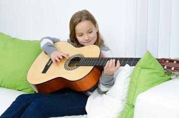 Mädchen hat Spaß am Gitarre spielen