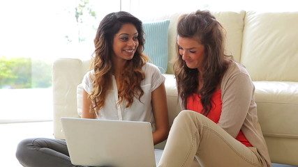 Women sitting in front of the couch with laptop
