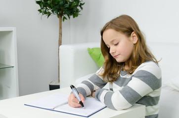 Mädchen macht Hausaufgaben am Wohnzimmertisch
