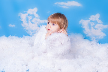 Baby with angel wings sitting in the clouds