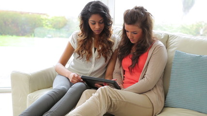 Women sitting on the couch while holding a tablet PC