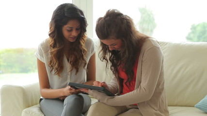 Women sitting on the couch holding a tablet PC