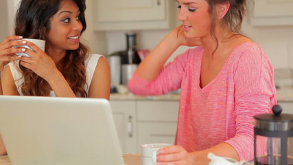 Women drinking coffee and looking at laptop