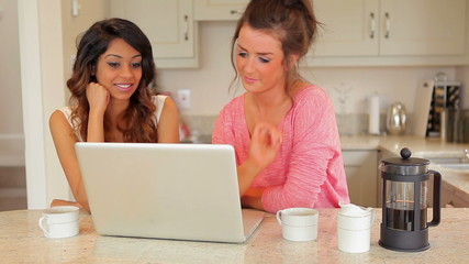 Women drinking coffee while looking at laptop