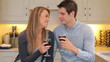 Couple sitting in the kitchen drinking wine