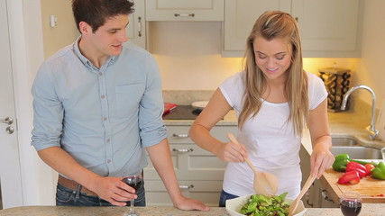 Woman tossing salad and man drinking wine