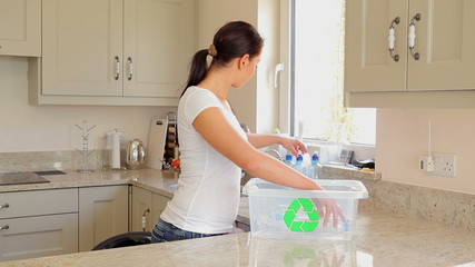 Woman putting bottles into recycling bin