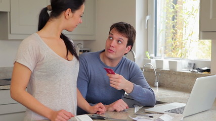 Couple discussing finances at laptop and cutting credit card