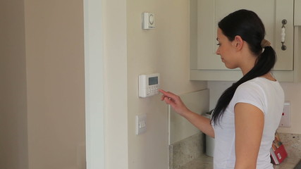 Woman turning on alarm system
