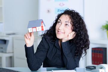 geschäftsfrau mit miniaturhaus