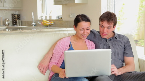 Couple sitting on the sofa and talking on video chat