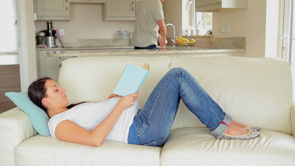Pregnant woman relaxing on sofa with book
