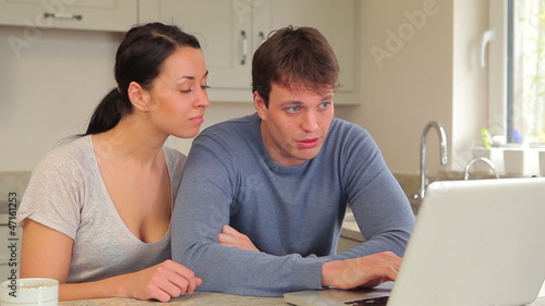 Couple talking and looking at laptop