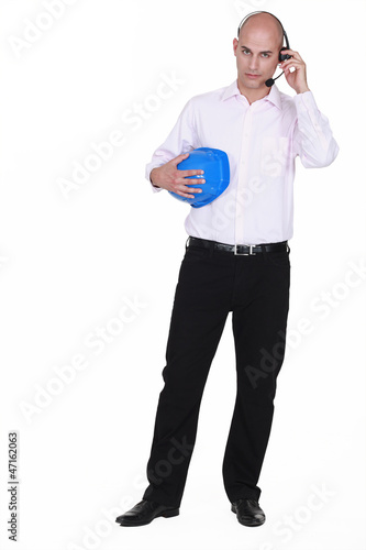 businessman with headset holding hard hat