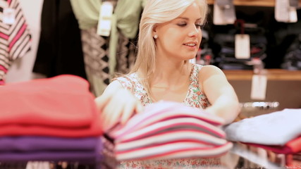 Woman folding clothes and smiling