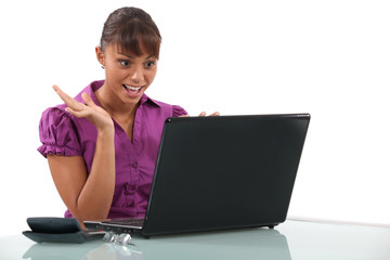 Office worker looking at her laptop in glee