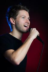 junger mann singt mit mikrofon