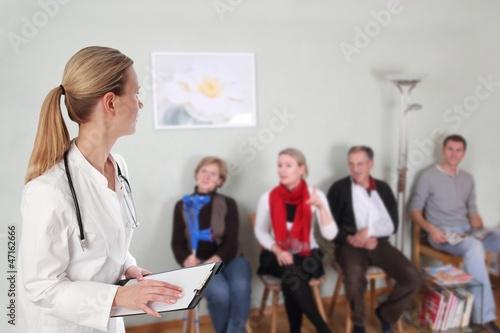 Leinwanddruck Bild Ärztin im Wartezimmer mit Patienten
