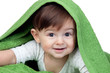 Happy baby covered with a green towel