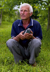 An elderly man with a dove in his hands
