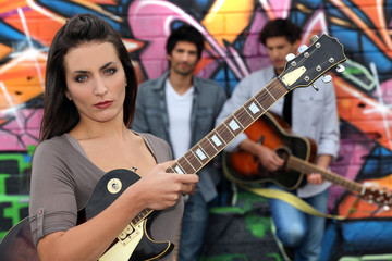 Female guitarist standing with band members