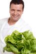 junger mann präsentiert grünen kopfsalat