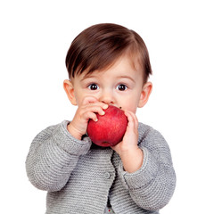 Adorable baby girl eating a red apple