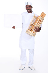Baker with a basket of baguettes and a board for message