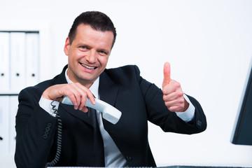 lachender manager zeigt daumen hoch