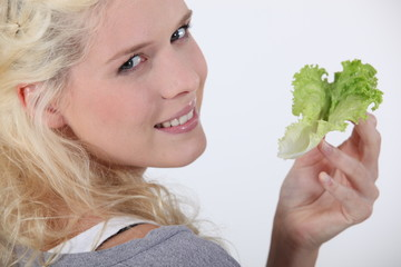 Attractive blond woman holding lettuce leaf