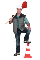 road worker holding a shovel and a traffic cone