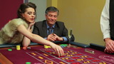 Woman and man placing bets on roulette table