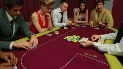 People playing poker waiting for dealer