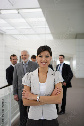 smiling businesswoman standing cross-armed in workplace