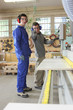 Carpenter and apprentice using industrial saw