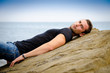 Handsome male model lying on sea rock