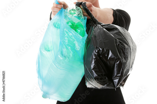 Young man carrying a plastic trash bags.