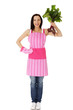 Woman in  pink kitchen appron holding beetroot.