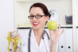 Woman dietician holding apple and  measuring tape